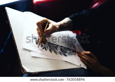 Male artist with tattoo on her hand in a dark room draws a picture pencils