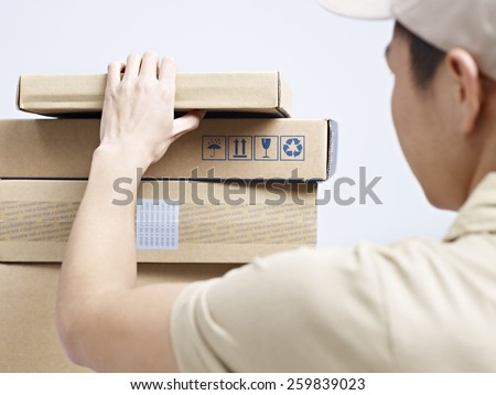 male asian courier company worker checking packages to be delivered.