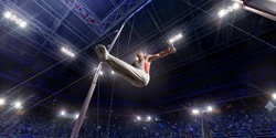 Male athlete doing a complicated exciting trick on gymnastics rings in a professional gym. Man perform stunt in bright sports clothes