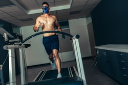Male athlete examining his fitness in sports lab. Runner with mask doing a performance test on treadmill.