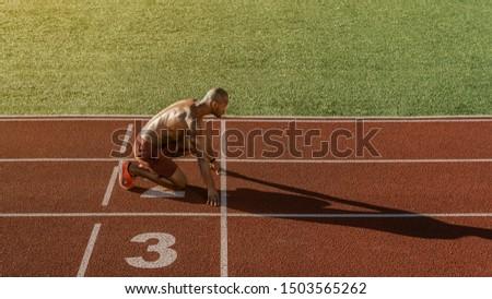 Male athlete on starting position at athletics running track on stadium