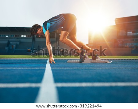 Male athlete on starting position at athletics running track. Runner practicing his sprint start in athletics stadium racetrack.