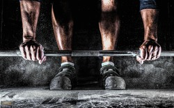 Male athlete preparing for barbell workout in gym. Weightlifting, power lifting training, fitness, sports concept.