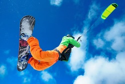 Male Athlete rides in the winter snowboarding and controls the kite. A clear winter day with clouds. Performs stunts and jumps