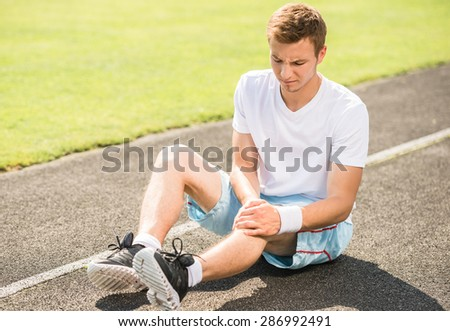 Male athlete runner touching foot in pain due to sprained ankle.