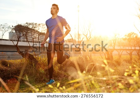 Male athlete running in the park at sunset (little motion blur, intentional sun glare)