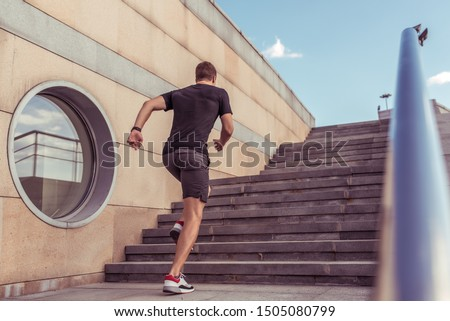 male athlete runs up stairs in summer city, view from the back, free space for text. Active lifestyle, health fitness workout. Athletics guy in a t-shirt and shorts