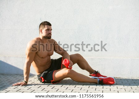 Male athlete taking break and holding protein shaker