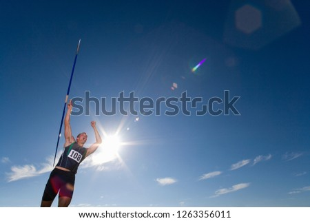 Male athlete throwing javelin at athletics event in stadium