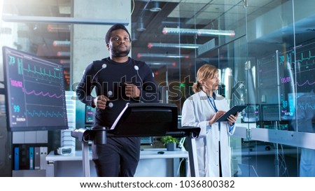 Male Athlete Walks on a Treadmill with Electrodes Attached to His Body while Sport Scientist Interacts with Touchscreen and Supervises EKG Status. In the Background Laboratory with High-Tech Equipment #1036800382