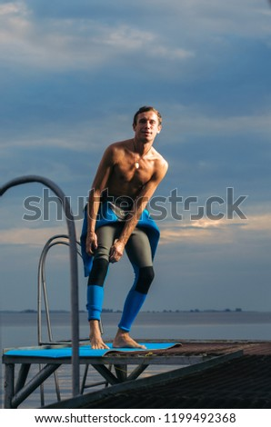 Male athlete wearing a thermal swimsuit. the man wears a wetsuit #1199492368