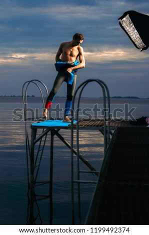 Male athlete wearing a thermal swimsuit. the man wears a wetsuit #1199492374