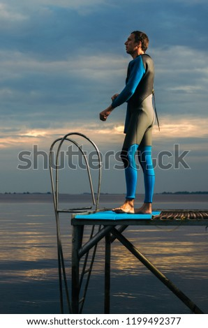 Male athlete wearing a thermal swimsuit. the man wears a wetsuit #1199492377