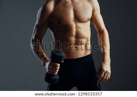 male athlete with a muscled naked body on a black isolated background sport fitness shakes his muscles with dumbbells