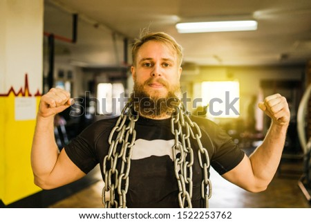Male athlete with beard posing at the gym flexing biceps muscles showing his strength with big chain around his neck after training