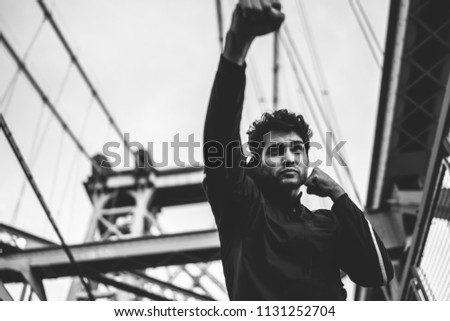 Male athlete with concentrated face practicing power punches with strength on city bridge during morning training, strong good looking man champ boxing and preparing for fight on urban setting