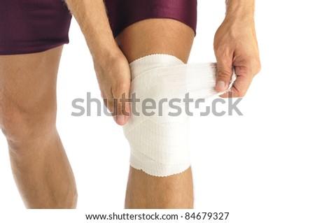 Male athlete wraps knee injury with bandage