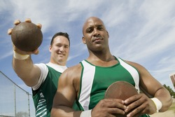 Male athletes holding shot put and discus