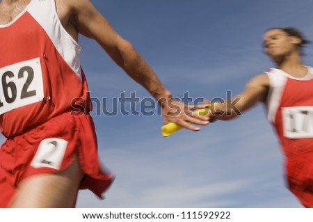 Stock Photo Male athletes passing baton in relay race