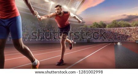 Male athletes sprinting. Runner passes the baton at the running track in professional stadium