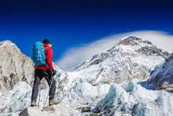 Male backpacker enjoying the view on mountain walk in Himalayas. Face to face with mount Everest, Earth's highest mountain. Travel, adventure, sport concept
