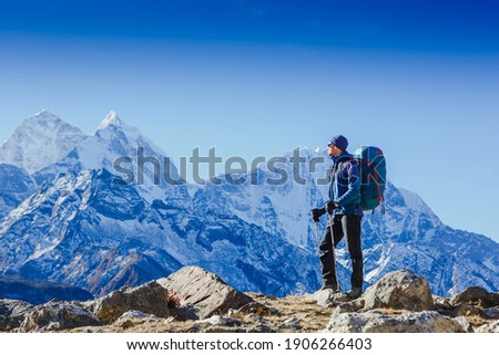 Male backpacker enjoying the view on mountain walk in Himalayas. Travel, adventure, sport concept