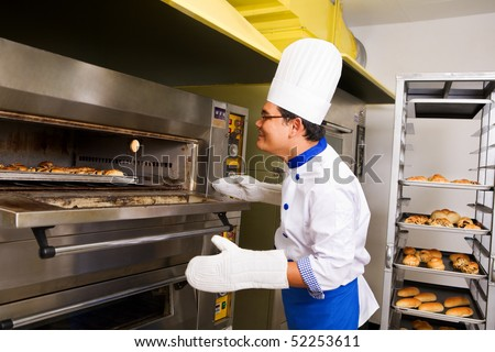 Male baker checking the bread inside oven