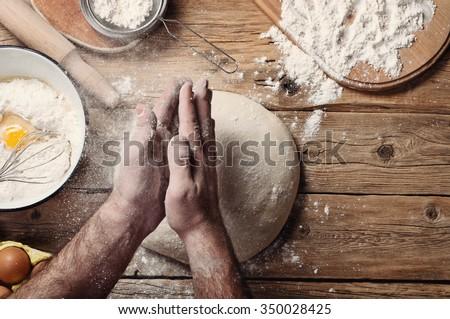 Male baker prepares bread. Male baker slaps on dough. Making  bread. Top view. Rustic style