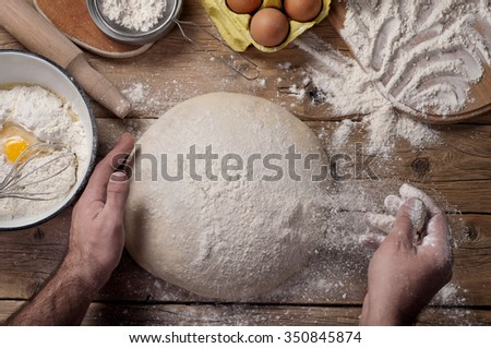 Male baker prepares bread. Male baker sprinkle the dough with flour. Making bread. Top view. Rustic style