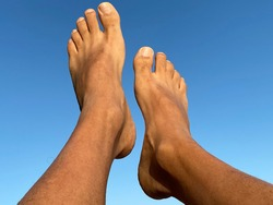 Male bare feet  against blue background