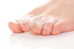 Male bare feet in bunion correctors for treat pain in hallux valgus on white background.