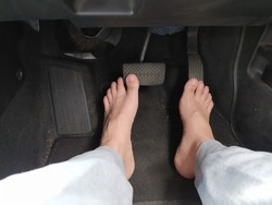 Male bare feet on the brake and accelerator pedals in a car