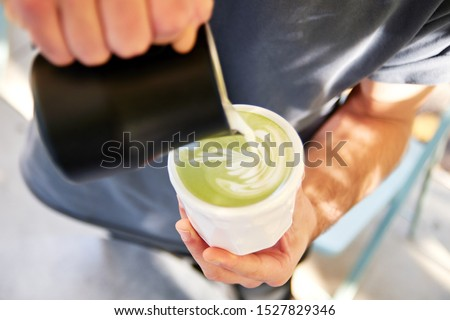 Male barista making vegan matcha cappuccino with oat milk with latte art in outdoor cafe.