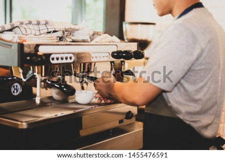 Male barista preparing coffee for the client.
