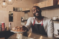 Male barista serves a croissant ordered to client. Afro american male barista working in cafe. A smiling young man serves cafe visitors. The concept of the restaurant business.