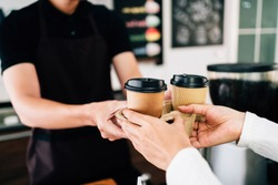 Male barista serving coffee in takeaway paper disposable cups in the coffee shop. Small green business during coronavirus pandemic.