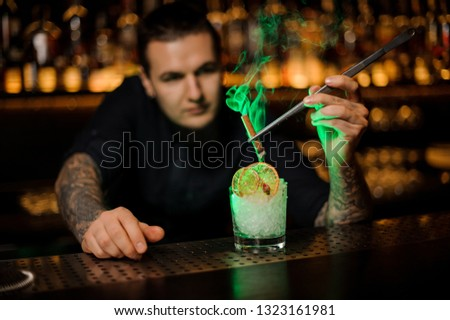 Male bartender adding to the glass with a dried orange and crushed ice aromatic smoked cinnamon with tweezers on the bar counter #1323161981