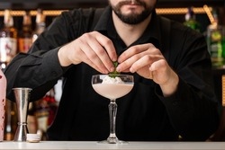 Male bartender decorates cocktail with ice cream and baileys in glass on bar counter