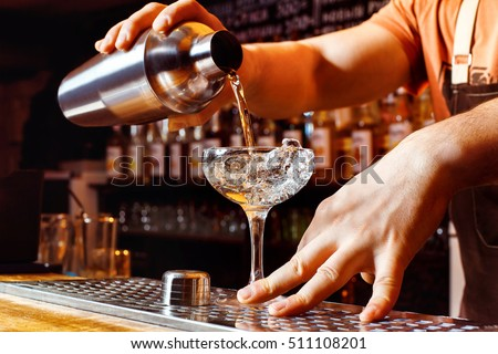 Male bartender is making cocktail pouring alcohol from shaker to glass at bar background. Barman at work. #511108201