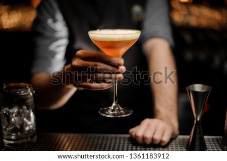 Male bartender serving cocktail with a whipped cream and grated nutmeg on the bar counter in the dark blurred background