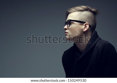 Male beauty concept. Portrait of fashionable young man with stylish haircut wearing trendy glasses and sweater, posing over gray background. Perfect hair & skin. Hipster style. Copy-space. Studio shot