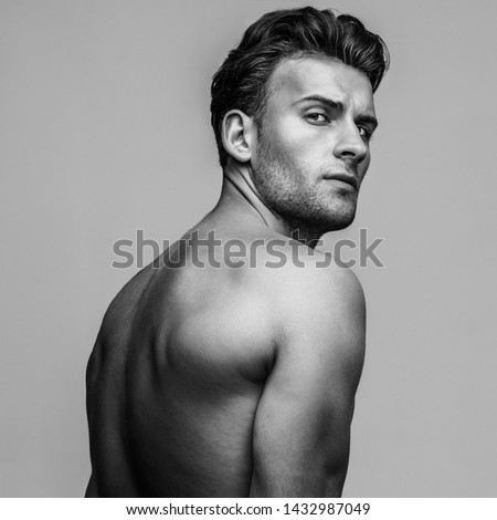 Male beauty concept. Portrait of handsome young man with stylish haircut posing over gray background. Perfect hair & skin. Tough guy. Vogue style. Close up. Studio shot