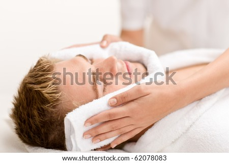 Male beauty - man at luxury spa treatment receiving facial massage