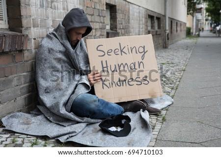 Male Beggar In Hood Showing Seeking Human Kindness Sign On Cardboard