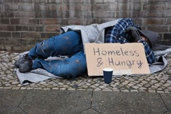 Male Beggar Lying On Street With Homeless And Hungry Text On Cardboard