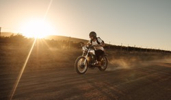 Male biker driving a vintage motorcycle on dirt road. Man riding fast on his bike on countryside road.