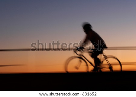 Male biker having an evening ride along the beach. Motion blur used to achieve dynamic photo