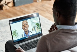Male black patient on conference video call with female african doctor. Virtual therapist consulting young man during online appointment on laptop at home. Telemedicine chat, telehealth concept.