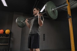 Male bodybuilder doing military press at dark gym. Weightlifter holding barbell on chest, preparing to lift it overhead or do front squat.Muscular fitness man lifting weight, having crossfit training