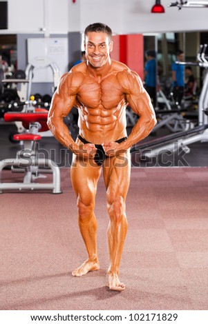 male bodybuilder flexing his muscle in gym